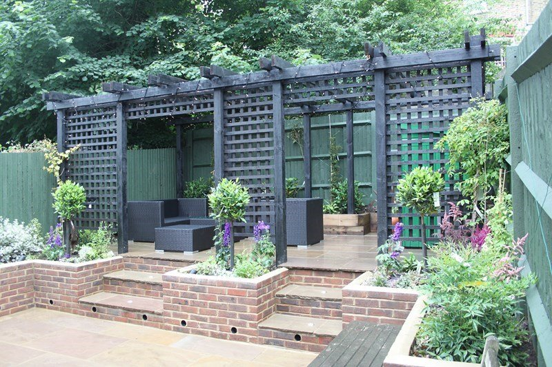 London Garden Builders design Large back garden  great idea Pergola with treelis, raised brick wall with steps and Indian Sandstone paving