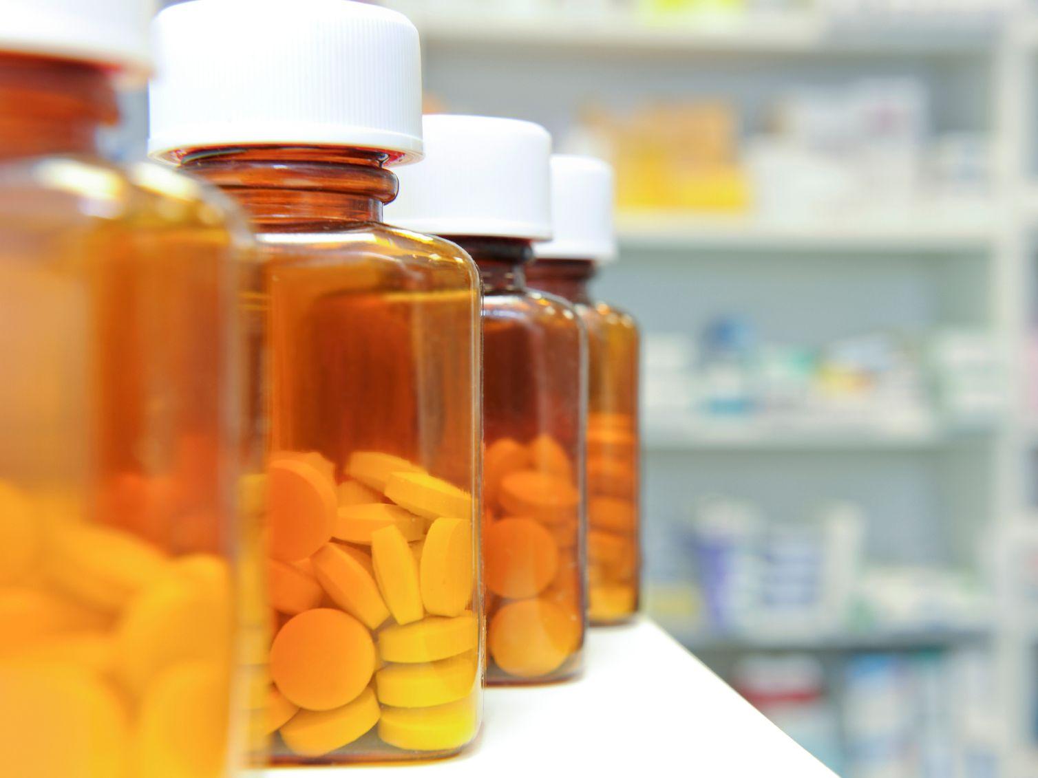 Pharmacist holding up medicine bottle