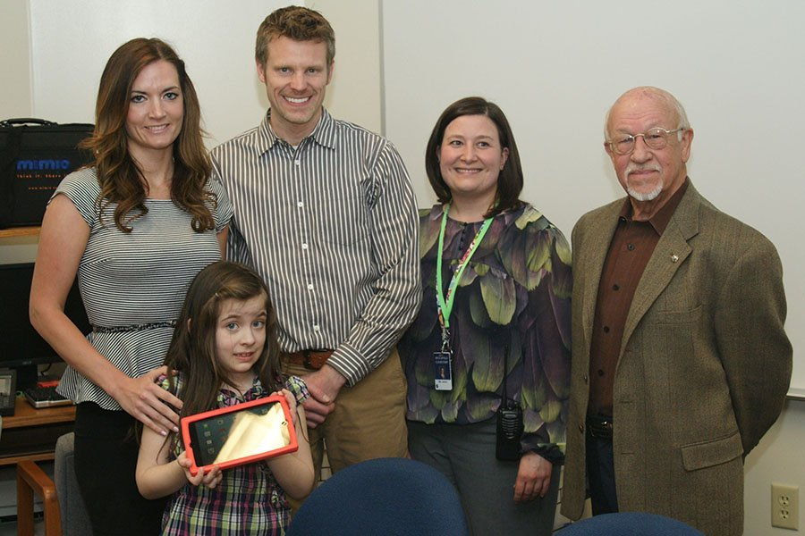A child on the autism spectrum receives an iPad from the Elm Grove Golden K Kiwanis Club.