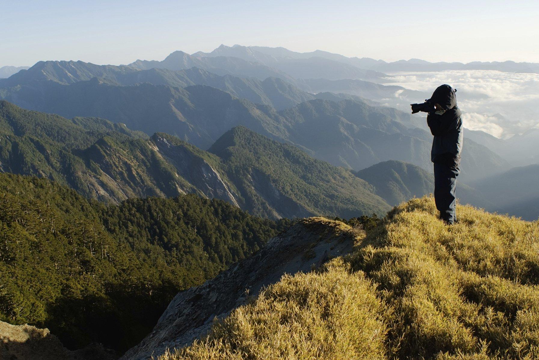 Person taking a photo atop a green mountain